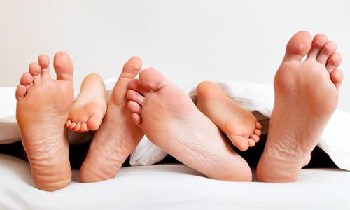 Fußsohlen einer Familie im Bett unter der Decke.
